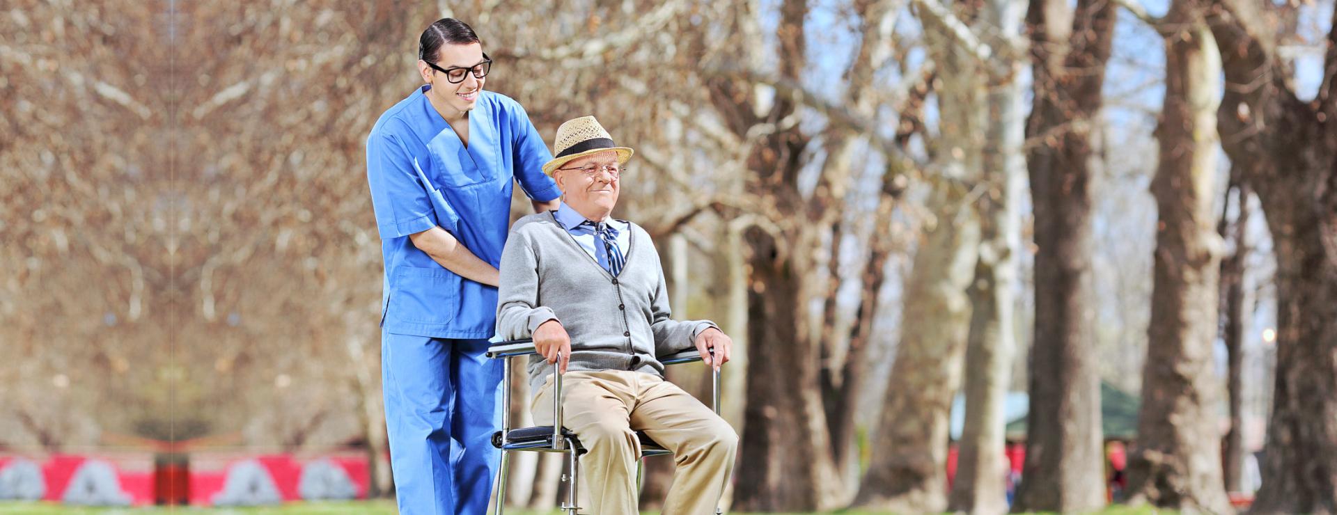 caregiver pushing an elderly man's wheelchair outdoors
