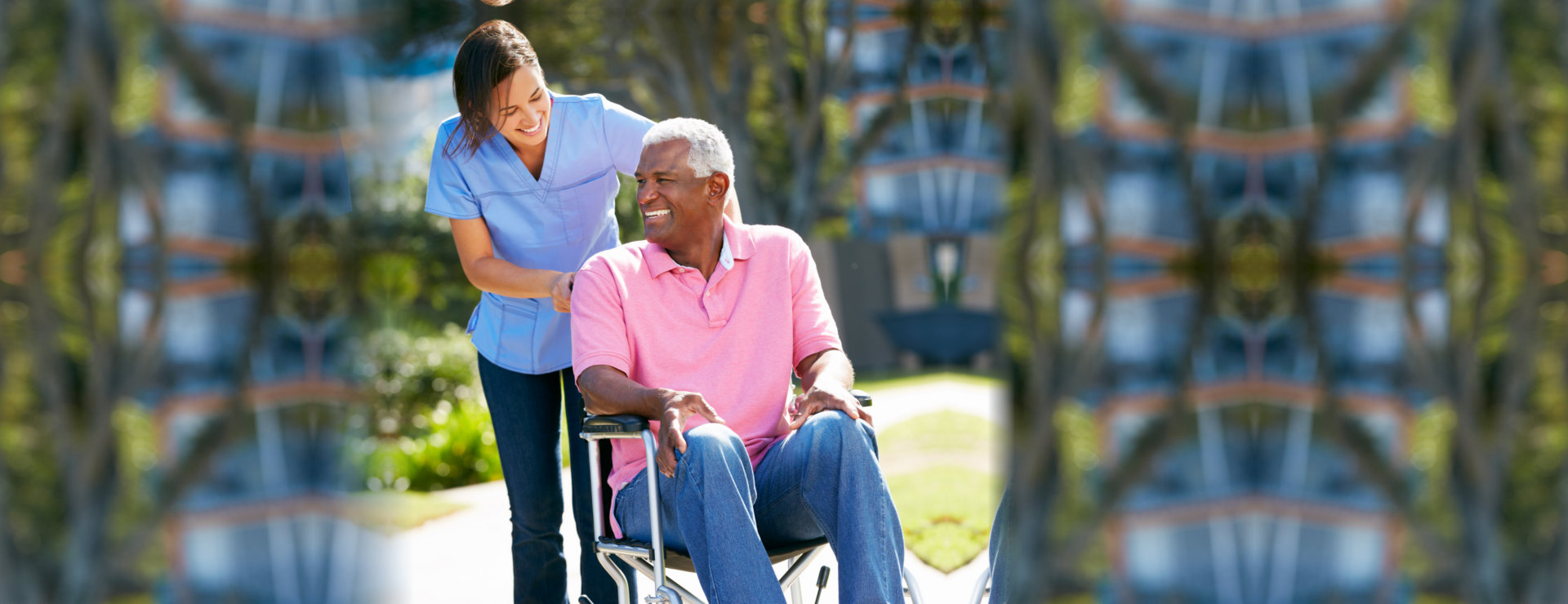 caregiver and elderly man in wheelchair smiling