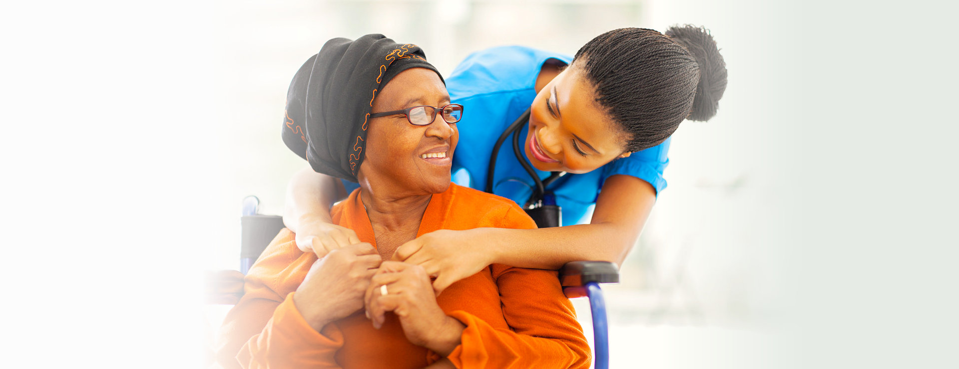 nurse and elderly woman in wheelchair smiling