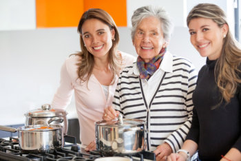 caregivers and elderly woman cooking together