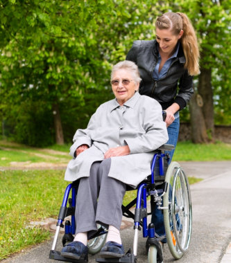 elderly woman in wheelchair together with her caregiver